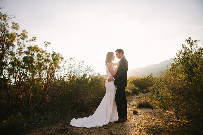 Anza valley rustic outdoor wedding at the alpaca farm bride chiffon gown with lace straps and open back design with wedding ring and groom navy blue suit with white dress shirt and no tie hugging at sunset wedding photo idea