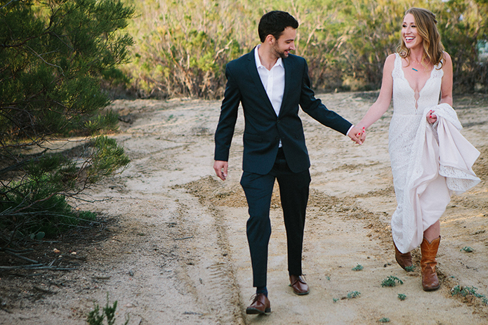 Anza valley rustic outdoor wedding at the alpaca farm bride chiffon gown with lace straps and open back design with wedding ring and groom navy blue suit with white dress shirt and no tie wedding photo idea walking holding up dress wearing cowboy boots