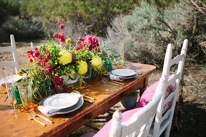 Anza valley rustic outdoor wedding at the alpaca farm brown wood table with white place settings and pink and yellow flower centerpiece with white chairs and pink pillow decor