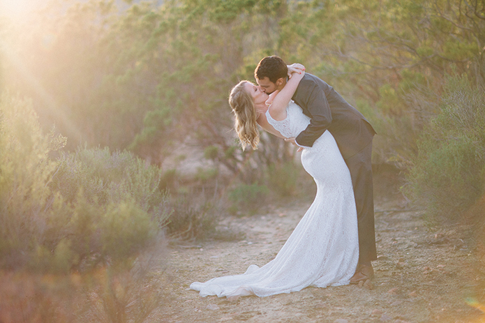 Anza valley rustic outdoor wedding at the alpaca farm bride chiffon gown with lace straps and open back design with wedding ring and groom navy blue suit with white dress shirt and no tie wedding photo idea kissing at sunset