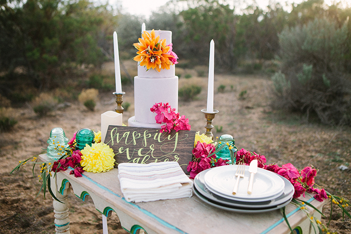 Anza valley rustic outdoor wedding at the alpaca farm white vintage table with three tier white wedding cake and pink and orange flower decor with white candles and brown wood sign with white calligraphy