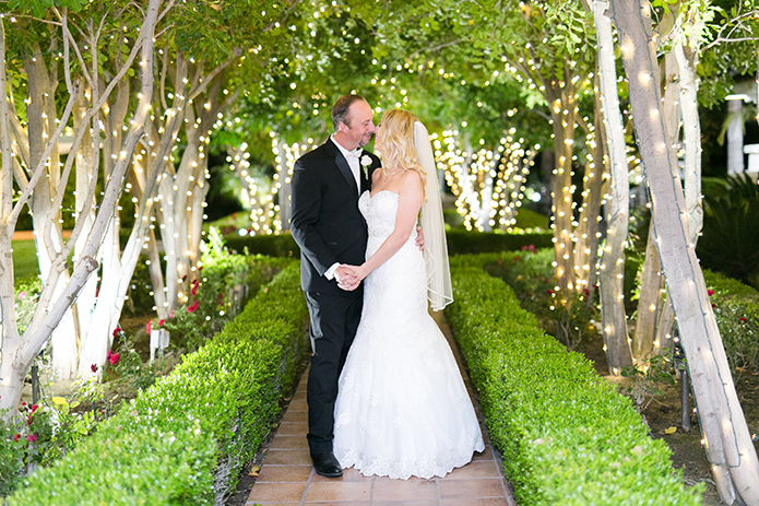 Temecula outdoor wedding at villa de amore vineyard bride strapless mermaid style gown with crystal belt and medium veil with groom black tuxedo with white dress shirt and white bow tie with matching vest and white floral boutonniere holding hands by trees with light decor