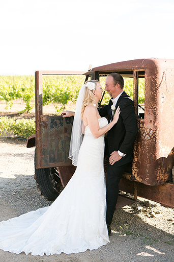 Temecula outdoor wedding at villa de amore vineyard bride strapless mermaid style gown with crystal belt and medium veil with groom black tuxedo with white dress shirt and white bow tie with matching vest and white floral boutonniere hugging by brown vintage truck
