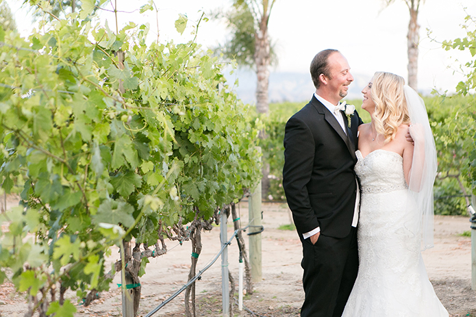 Temecula outdoor wedding at villa de amore vineyard bride strapless mermaid style gown with crystal belt and medium veil with groom black tuxedo with white dress shirt and white bow tie with matching vest and white floral boutonniere hugging in vineyard