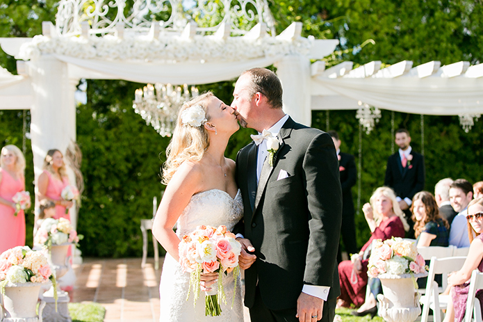 Temecula outdoor wedding at villa de amore vineyard bride strapless mermaid style gown with crystal belt and medium veil with groom black tuxedo with white dress shirt and white bow tie with matching vest and white floral boutonniere kissing at the end of the aisle after ceremony