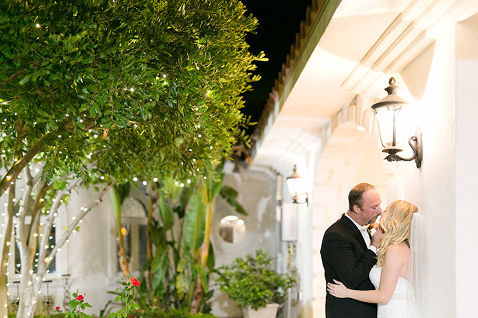Temecula outdoor wedding at villa de amore vineyard bride strapless mermaid style gown with crystal belt and medium veil with groom black tuxedo with white dress shirt and white bow tie with matching vest and white floral boutonniere kissing at night by wall