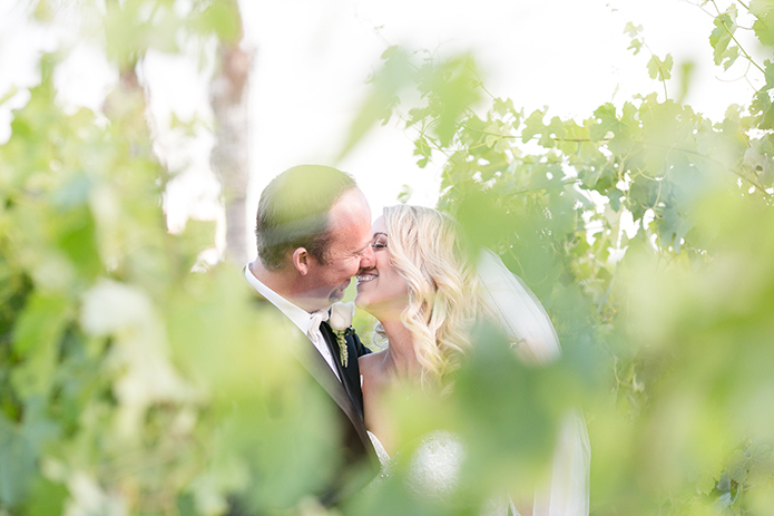 Temecula outdoor wedding at villa de amore vineyard bride strapless mermaid style gown with crystal belt and medium veil with groom black tuxedo with white dress shirt and white bow tie with matching vest and white floral boutonniere kissing in vineyard
