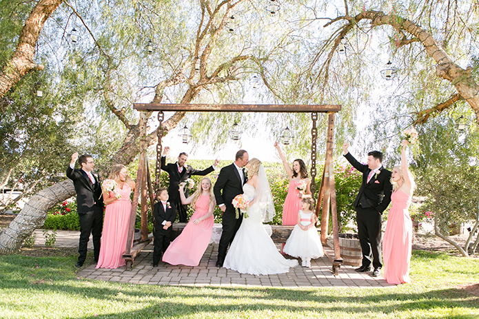 Temecula outdoor wedding at villa de amore vineyard bride strapless mermaid style gown with crystal belt and medium veil with groom black tuxedo with white dress shirt and white bow tie with matching vest and white floral boutonniere kissing with bridesmaids long pink dresses and groomsmen black tuxedo with pink bow ties cheering