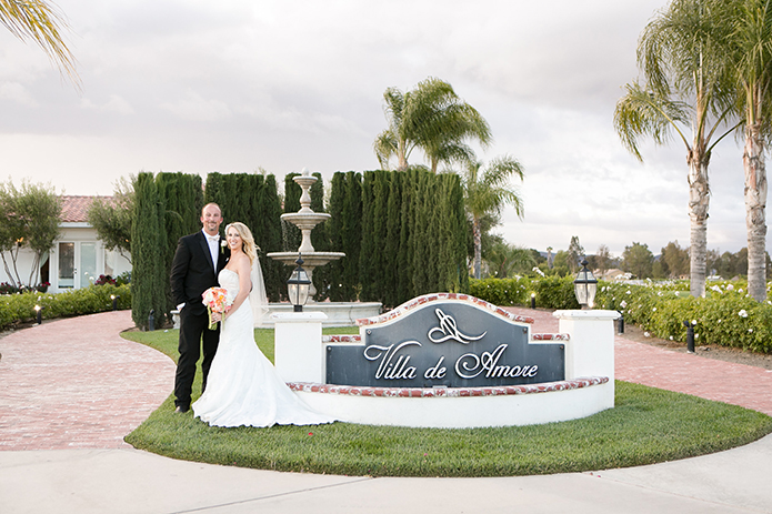 Temecula outdoor wedding at villa de amore vineyard bride strapless mermaid style gown with crystal belt and medium veil with groom black tuxedo with white dress shirt and white bow tie with matching vest and white floral boutonniere standing by vineyard sign