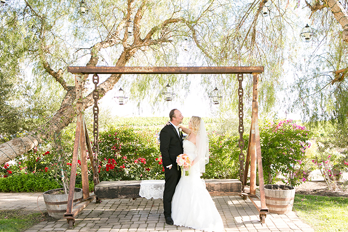 Temecula outdoor wedding at villa de amore vineyard bride strapless mermaid style gown with crystal belt and medium veil with groom black tuxedo with white dress shirt and white bow tie with matching vest and white floral boutonniere standing by brown wooden swing rustic decor
