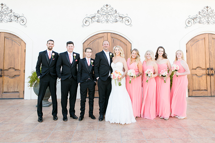 Temecula outdoor wedding at villa de amore vineyard bride strapless mermaid style gown with crystal belt and medium veil with groom black tuxedo with white dress shirt and white bow tie with matching vest and white floral boutonniere with bridesmaids long pink dresses and groomsmen black tuxedo with pink ties