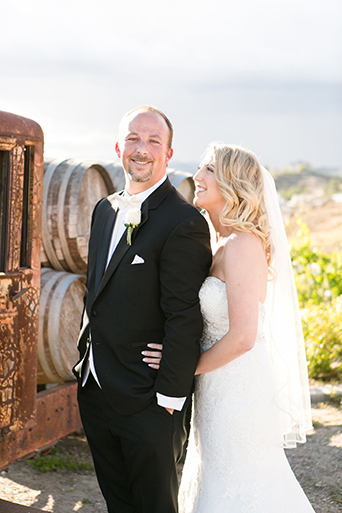 Temecula outdoor wedding at villa de amore vineyard bride strapless mermaid style gown with crystal belt and medium veil with groom black tuxedo with white dress shirt and white bow tie with matching vest and white floral boutonniere standing by brown vintage truck