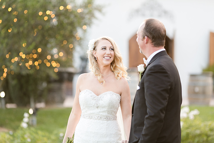 Temecula outdoor wedding at villa de amore vineyard bride strapless mermaid style gown with crystal belt and medium veil with groom black tuxedo with white dress shirt and white bow tie with matching vest and white floral boutonniere smiling