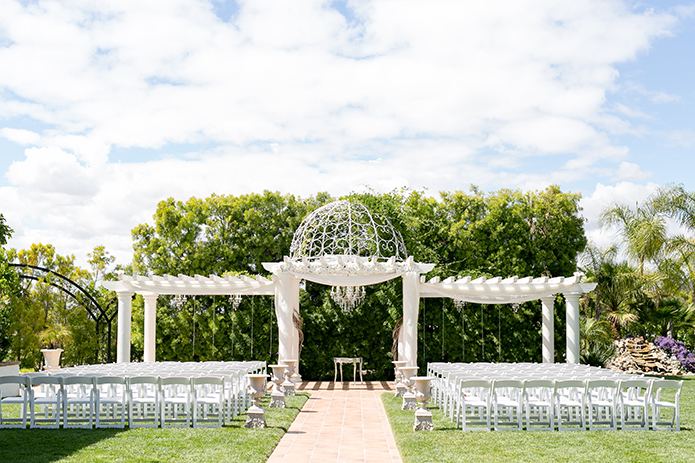 Temecula outdoor wedding at villa de amore vineyard ceremony set up with white chairs and white gazebo with white and pink flower decor wedding photo idea
