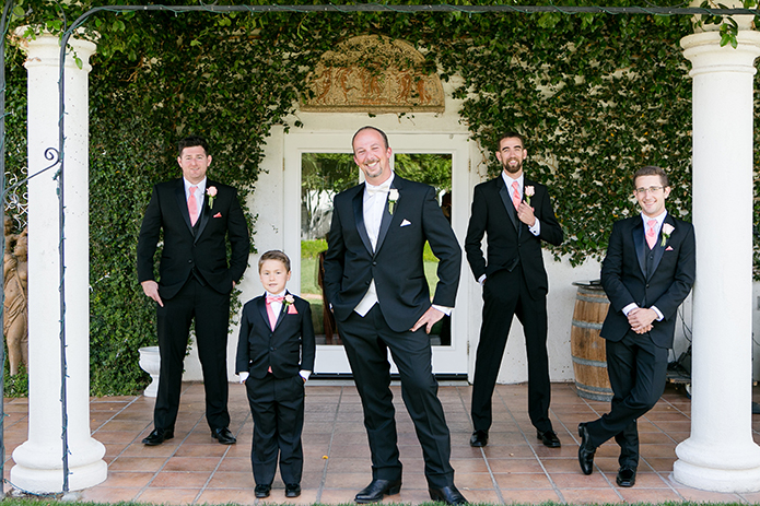 Temecula outdoor wedding at villa de amore vineyard groom black tuxedo with white dress shirt and white bow tie with matching vest with groomsmen black tuxedo with white dress shirt and long pink tie with pink vest and white floral boutonnieres
