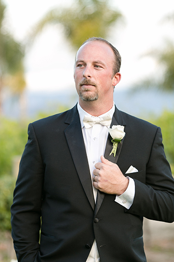 Temecula outdoor wedding at villa de amore vineyard groom black tuxedo with white dress shirt and white bow tie with matching vest and white floral boutonniere