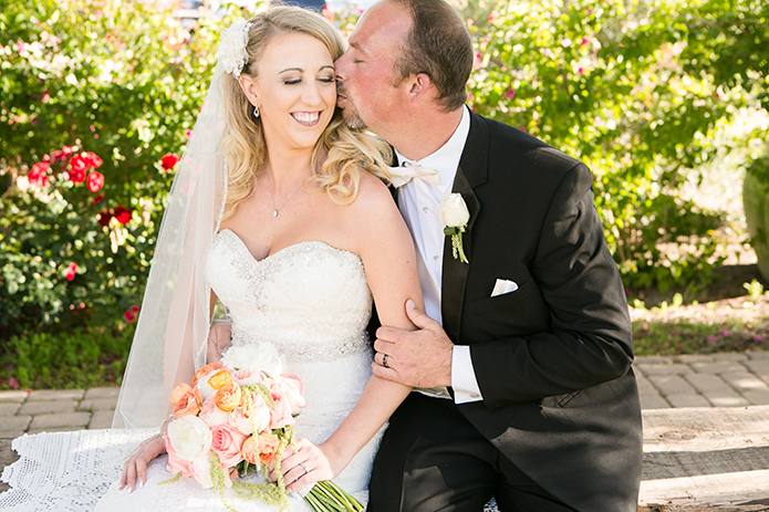 Temecula outdoor wedding at villa de amore vineyard bride strapless mermaid style gown with crystal belt and medium veil with groom black tuxedo with white dress shirt and white bow tie with matching vest and white floral boutonniere and white and pink floral bridal bouquet kissing bride