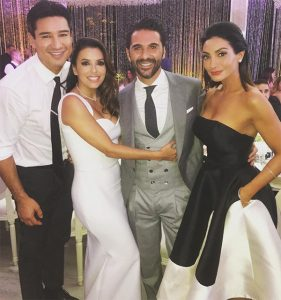 Celebrity wedding in mexico eva longoria mermaid style gown with straps and groom grey suit with white dress shirt and long black tie with matching vest standing with friends