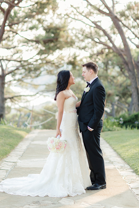 Summer outdoor wedding at south coast botanic gardens bride mermaid style gown with lace detail and sweetheart neckline with crystal belt and groom black suit with matching vest with white dress shirt and black bow tie with white floral boutonniere bride holding white floral bridal bouquet