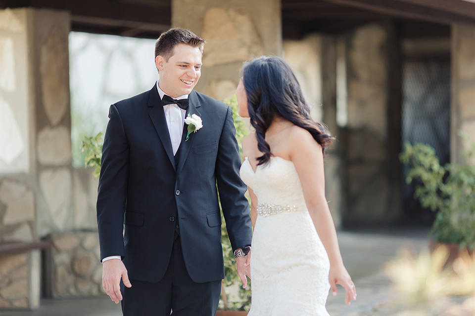 Summer outdoor wedding at south coast botanic gardens bride mermaid style gown with lace detail and sweetheart neckline with crystal belt and groom black suit with matching vest with white dress shirt and black bow tie with white floral boutonniere
