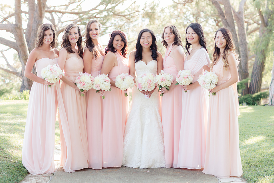 Summer outdoor wedding at south coast botanic gardens bride mermaid style gown with lace detail and sweetheart neckline with crystal belt with bridesmaids long blush pink dresses with white floral bridal bouquets