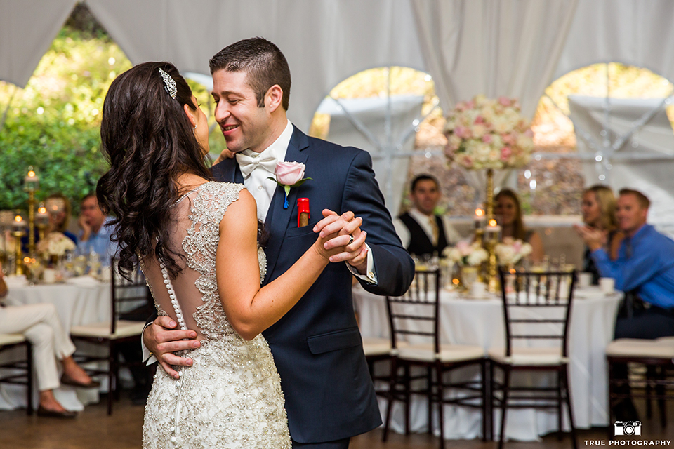 San diego outdoor wedding at the grand tradition bride mermaid style gown with illusion back and straps with plunging neckline and groom navy suit with matching vest and white dress shirt with white bow tie and white floral boutonniere dancing