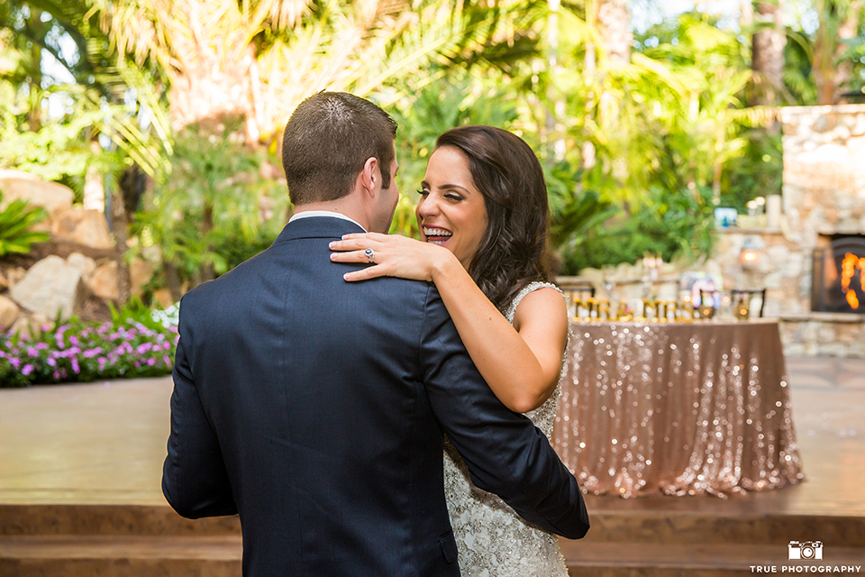 San diego outdoor wedding at the grand tradition bride mermaid style gown with illusion back and straps with plunging neckline and groom navy suit with matching vest and white dress shirt with white bow tie and white floral boutonniere first dance