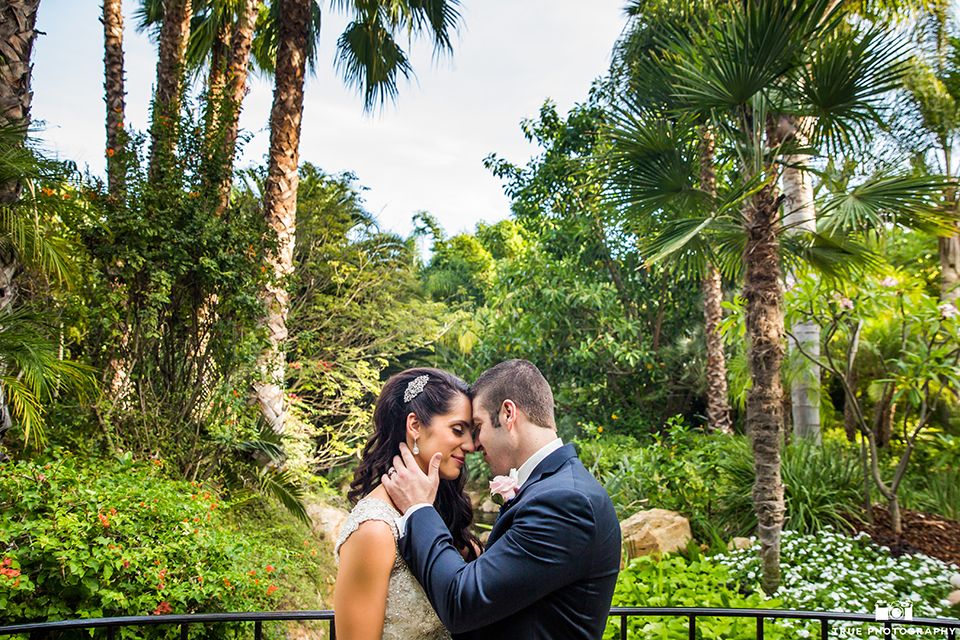 San diego outdoor wedding at the grand tradition bride mermaid style gown with illusion back and straps with plunging neckline and groom navy suit with matching vest and white dress shirt with white bow tie and white floral boutonniere hugging