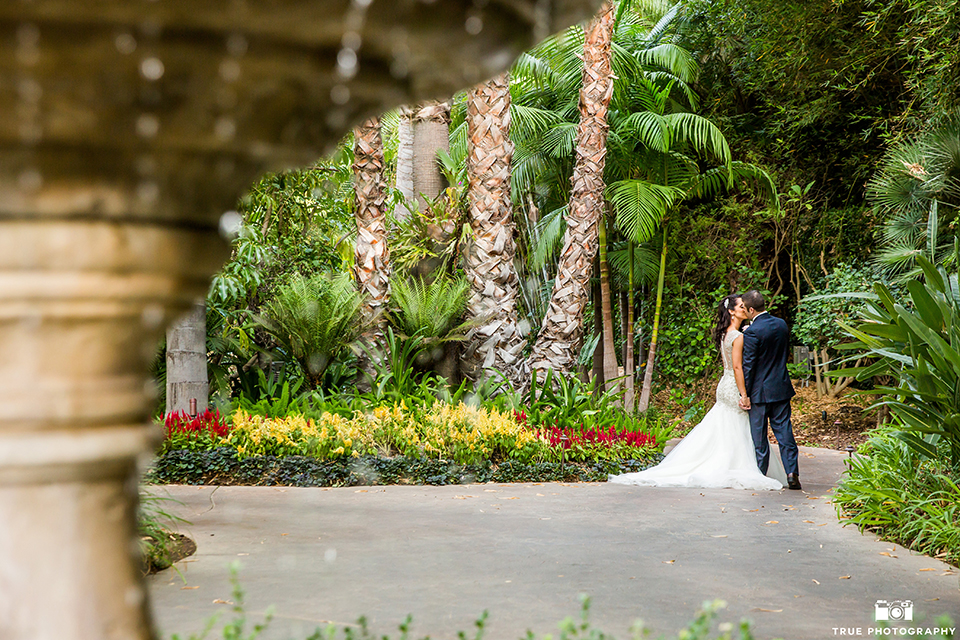 San diego outdoor wedding at the grand tradition bride mermaid style gown with illusion back and straps with plunging neckline and groom navy suit with matching vest and white dress shirt with white bow tie and white floral boutonniere kissing