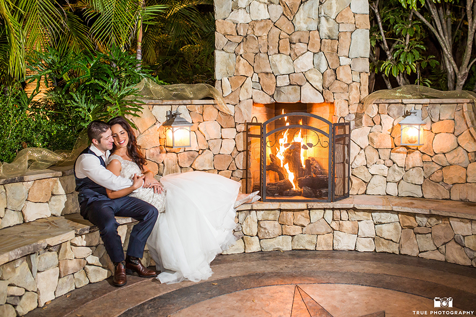 San diego outdoor wedding at the grand tradition bride mermaid style gown with illusion back and straps with plunging neckline and groom navy suit with matching vest and white dress shirt with white bow tie and white floral boutonniere sitting by fireplace