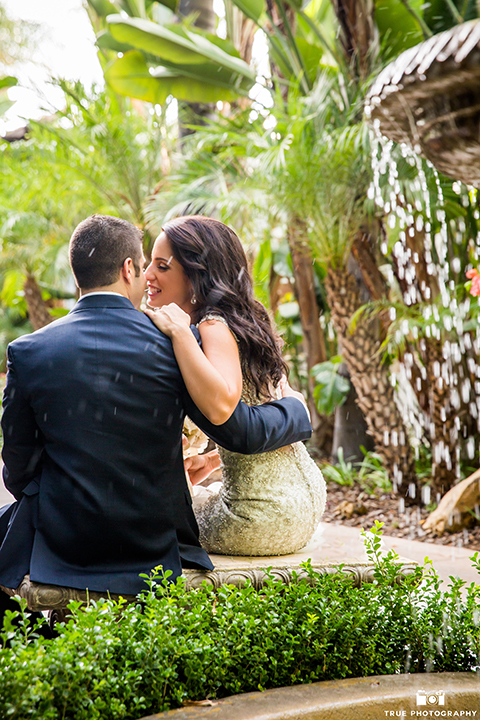San diego outdoor wedding at the grand tradition bride mermaid style gown with illusion back and straps with plunging neckline and groom navy suit with matching vest and white dress shirt with white bow tie and white floral boutonniere sitting by fountain hugging