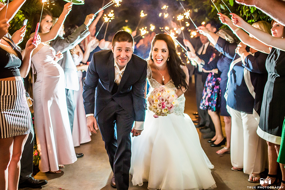 San diego outdoor wedding at the grand tradition bride mermaid style gown with illusion back and straps with plunging neckline and groom navy suit with matching vest and white dress shirt with white bow tie and white floral boutonniere sparkler exit