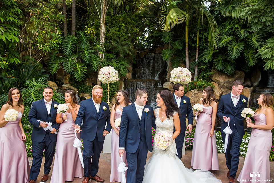 San diego outdoor wedding at the grand tradition bride mermaid style gown with illusion back and straps with plunging neckline and groom navy suit with matching vest and white dress shirt with white bow tie and white floral boutonniere with bridesmaids long pink dresses with groomsmen navy suits with long ties
