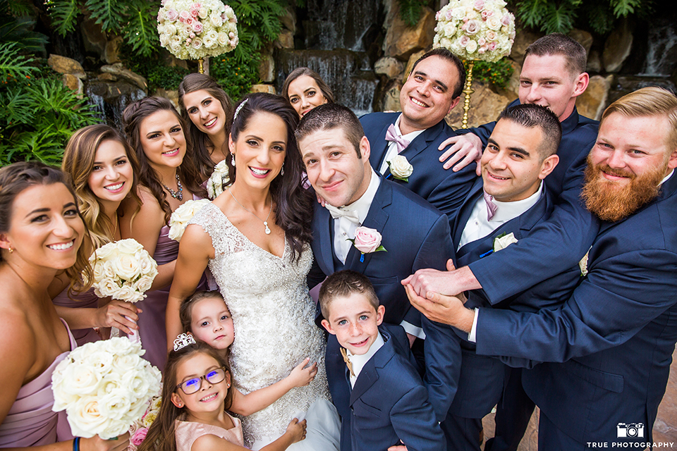 San diego outdoor wedding at the grand tradition bride mermaid style gown with illusion back and straps with plunging neckline and groom navy suit with matching vest and white dress shirt with white bow tie and white floral boutonniere with bridesmaids long pink dresses with groomsmen navy suits and long ties