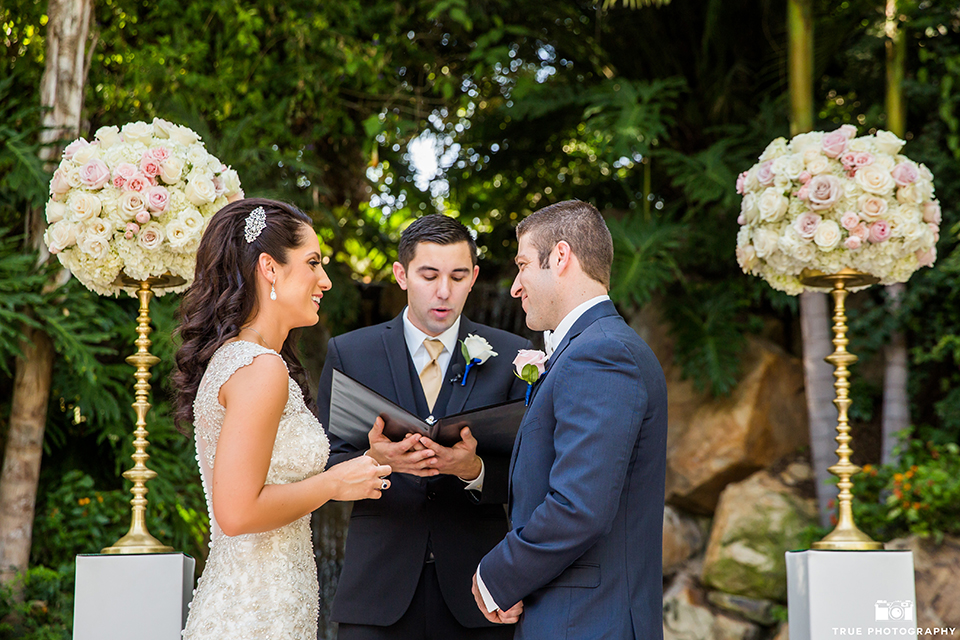 San diego outdoor wedding at the grand tradition bride mermaid style gown with illusion back and straps with plunging neckline and groom navy suit with matching vest and white dress shirt with white bow tie and white floral boutonniere standing during ceremony