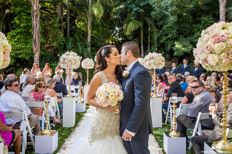 San diego outdoor wedding at the grand tradition bride mermaid style gown with illusion back and straps with plunging neckline and groom navy suit with matching vest and white dress shirt with white bow tie and white floral boutonniere kissing after ceremony