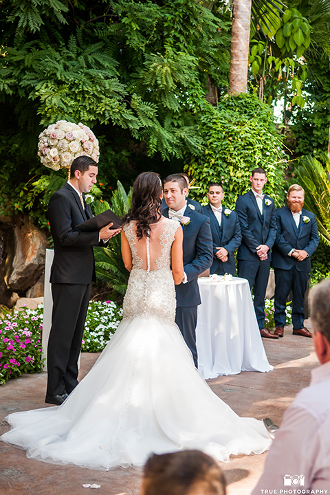 San diego outdoor wedding at the grand tradition bride mermaid style gown with illusion back and straps with plunging neckline and groom navy suit with matching vest and white dress shirt with white bow tie and white floral boutonniere holding hands during ceremony