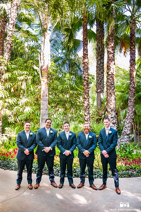San diego outdoor wedding at the grand tradition groom navy suit with matching vest and white dress shirt with white bow tie and white floral boutonniere with groomsmen navy suits with matching vest and white dress shirt with long white ties and white floral boutonnieres