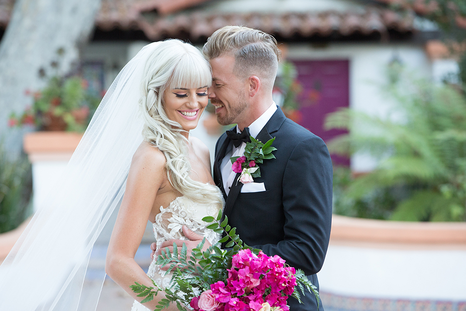 Rancho las lomas outdoor wedding shoot bride strapless tulle ballgown with beaded bodice and sweetheart neckline with long lace detail veil and groom black notch lapel tuxedo with white dress shirt and black bow tie with bright pink floral boutonniere hugging and bride holding bright pink floral bridal bouquet