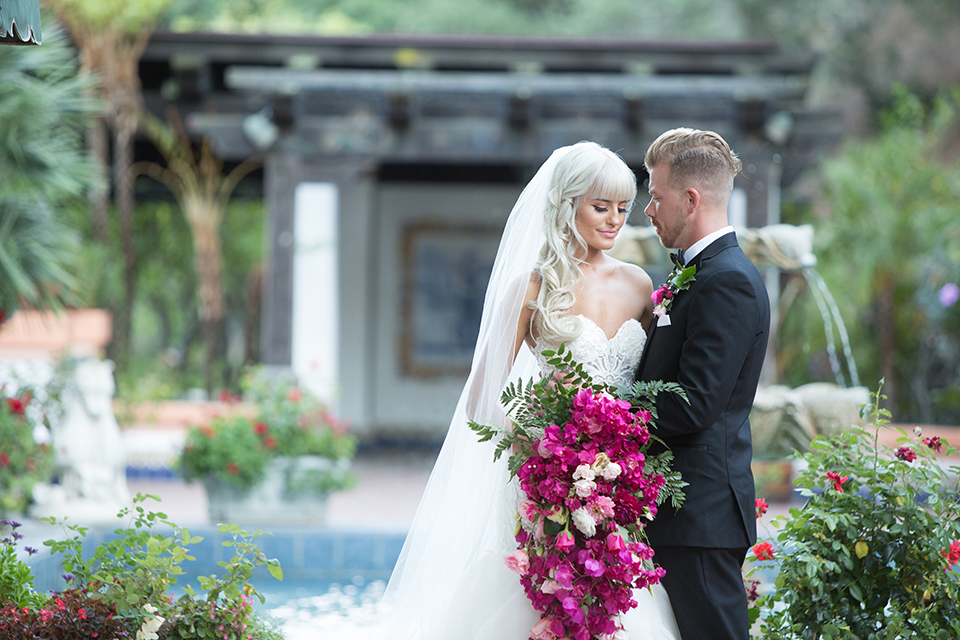 Rancho las lomas outdoor wedding shoot bride strapless tulle ballgown with beaded bodice and sweetheart neckline with long lace detail veil and groom black notch lapel tuxedo with white dress shirt and black bow tie with bright pink floral boutonniere hugging bride holding bright pink floral bridal bouquet