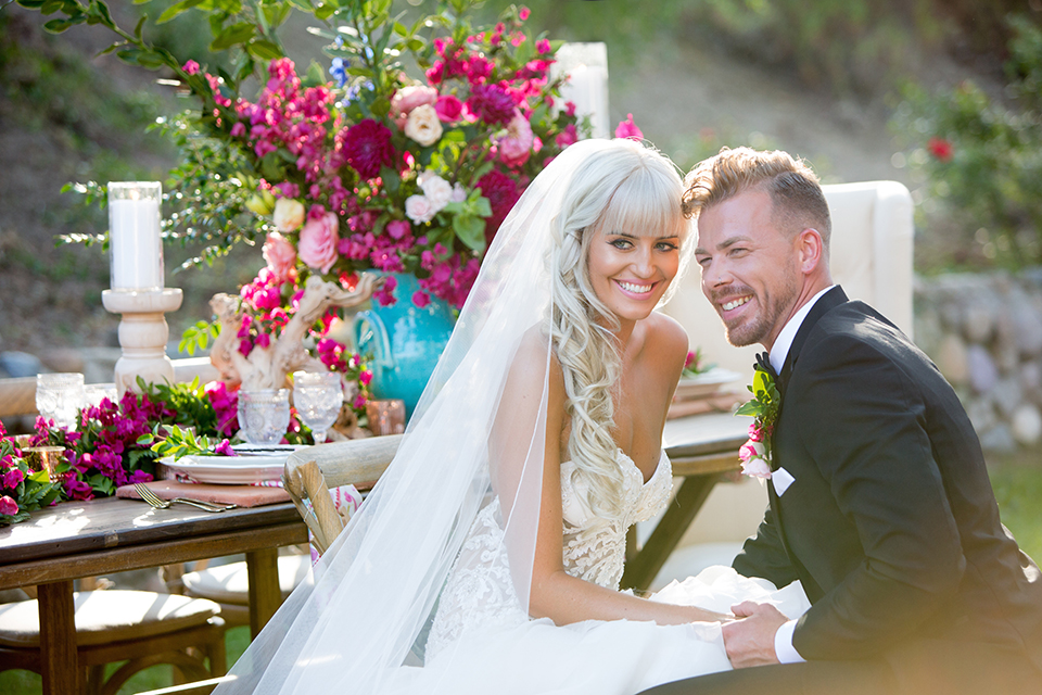 Rancho las lomas outdoor wedding shoot bride strapless tulle ballgown with beaded bodice and sweetheart neckline with long lace detail veil and groom black notch lapel tuxedo with white dress shirt and black bow tie with bright pink floral boutonniere bride holding bright pink floral bridal bouquet sitting at table and smiling