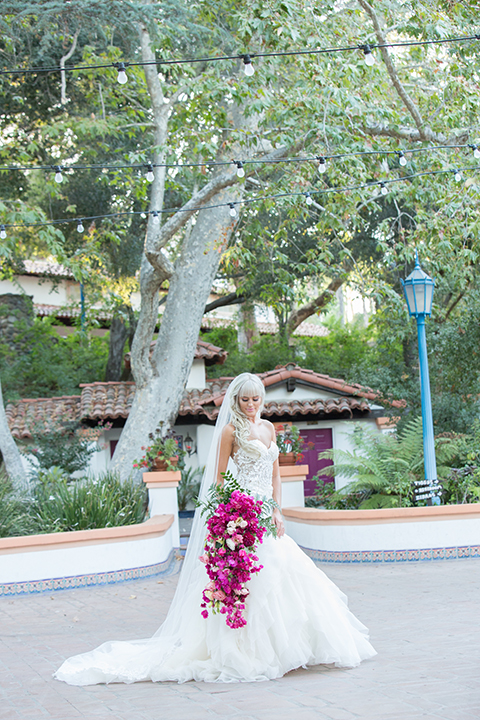 Rancho las lomas outdoor wedding shoot bride strapless tulle ballgown with beaded bodice and sweetheart neckline with long lace detail veil holding bright pink floral bridal bouquet