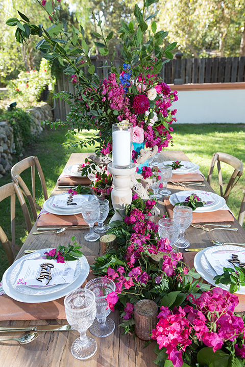 Rancho las lomas outdoor wedding shoot table set up light brown wood table with white place settings and bright pink flower decor with white candle centerpieces and light brown and white wood chairs with big white vintage chairs