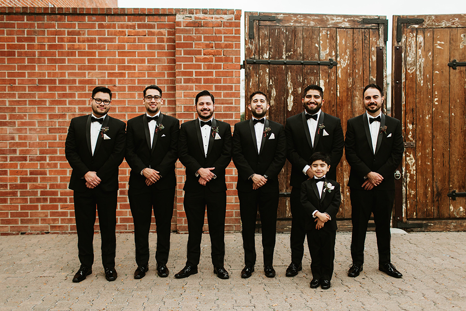 Orange county wedding at the estate on second groom black notch lapel tuxedo with white dress shirt and black bow tie with white pocket square with groomsmen and ring bearer black tuxedos with white shirts and black bow ties