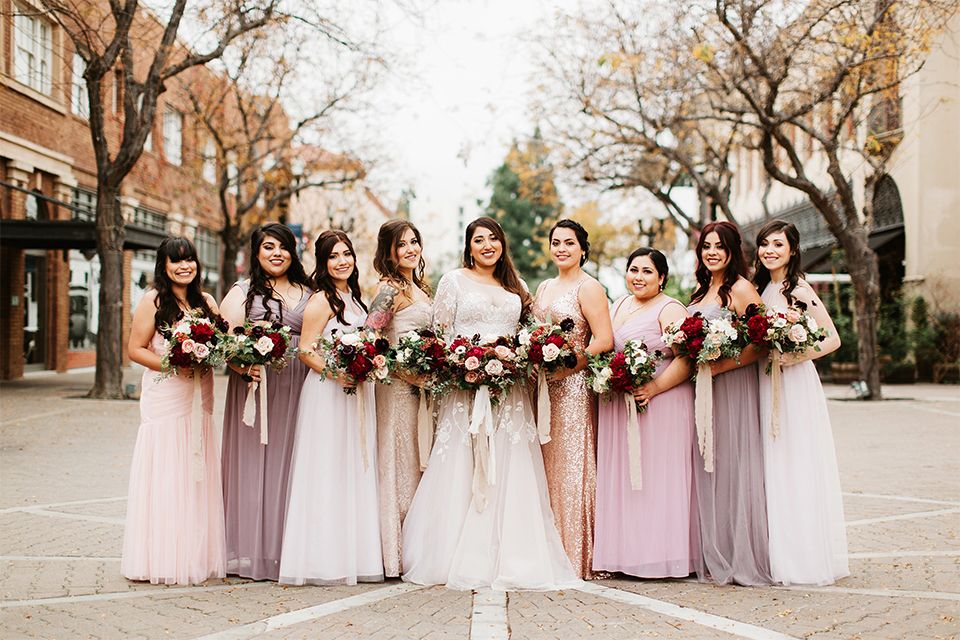 Orange county wedding at the estate on second bride lace ball gown with long sleeves and high neckline with crystal hair piece holding pink and red floral bridal bouquet with bridesmaids long mix and matched dresses pink and gold and purple holding floral bouquets