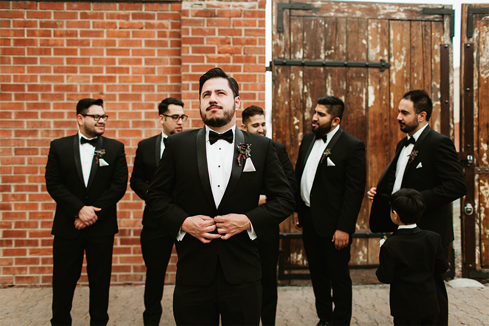 Orange county wedding at the estate on second groom black notch lapel tuxedo with white dress shirt and black bow tie with white pocket square with groomsmen black tuxedos with white shirts and black bow ties