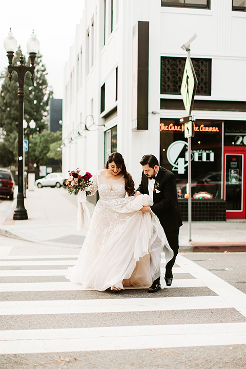 Orange county wedding at the estate on second bride lace ball gown with long sleeves and high neckline with crystal hair piece and groom black tuxedo with white dress shirt and black bow tie with white pocket square walking across the street bride holding pink and red floral bridal bouquet