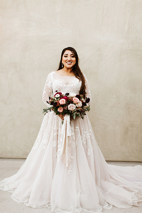 Orange county wedding at the estate on second bride lace ball gown with long sleeves and high neckline with crystal hair piece holding pink and red floral bridal bouquet