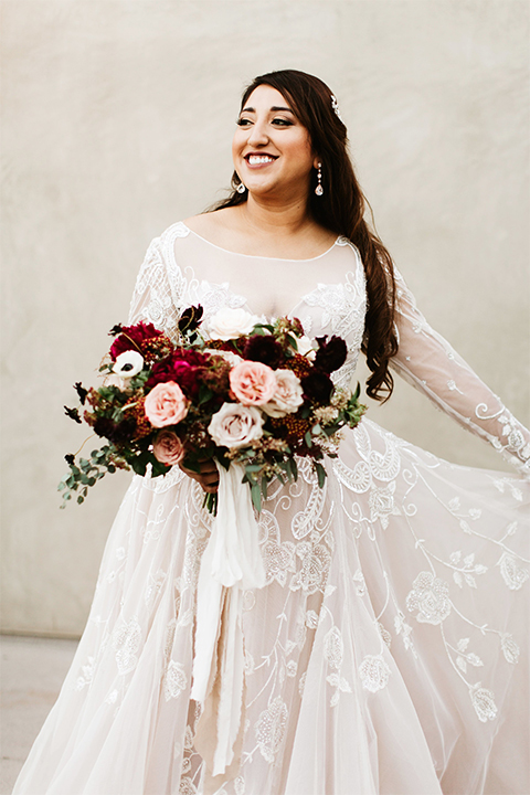 Orange county wedding at the estate on second bride lace ball gown with long sleeves and high neckline with crystal hair piece holding pink and red floral bridal bouquet holding dress