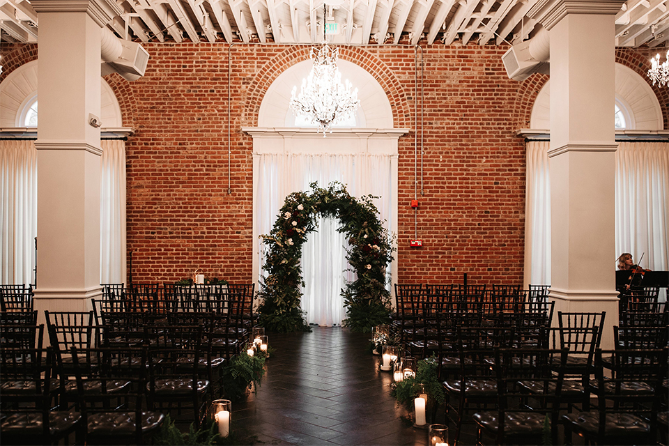 Orange county wedding at the estate on second ceremony set up with black chairs and dark brown hardwood floor with greenery floral arch at the end of the aisle with white candle decor on the ground